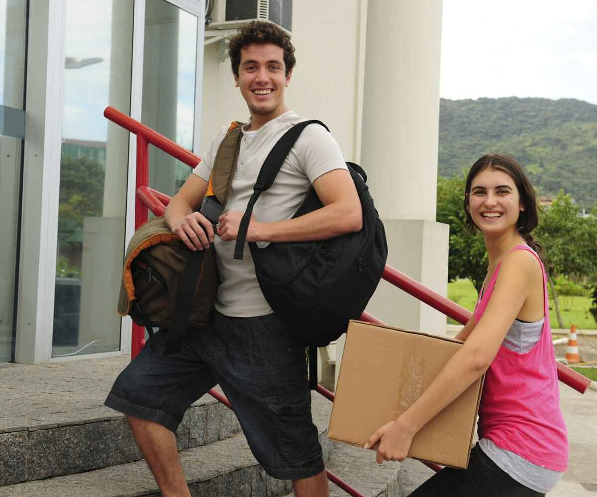Young sister helping her brother move into freshman year dorm on college move-in day