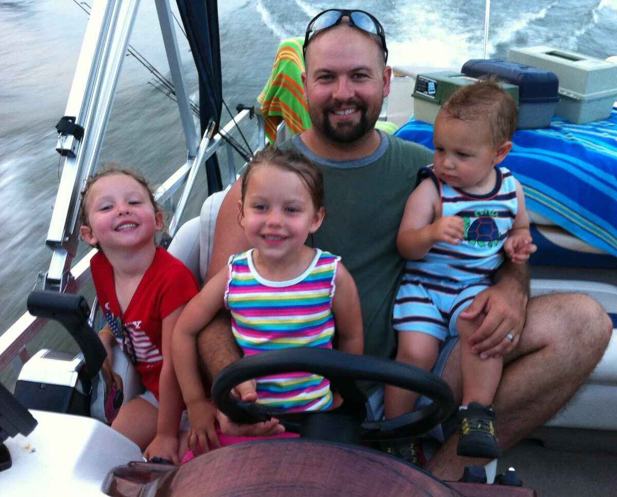 Dad driving boat with three children on his lap.