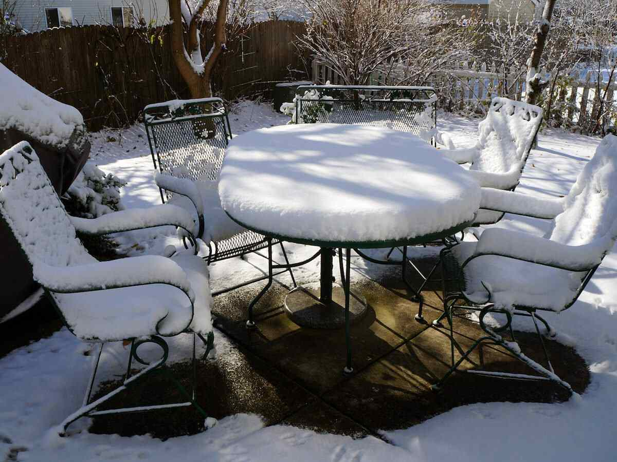 A patio furniture set improperly stored outside covered in snow