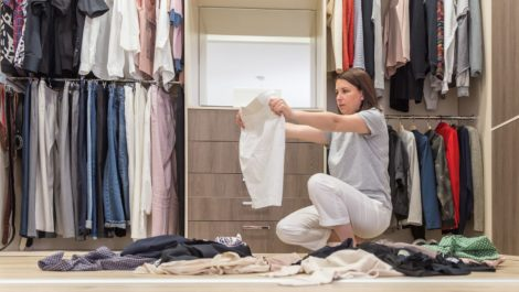 A woman organizing and decluttering her closet