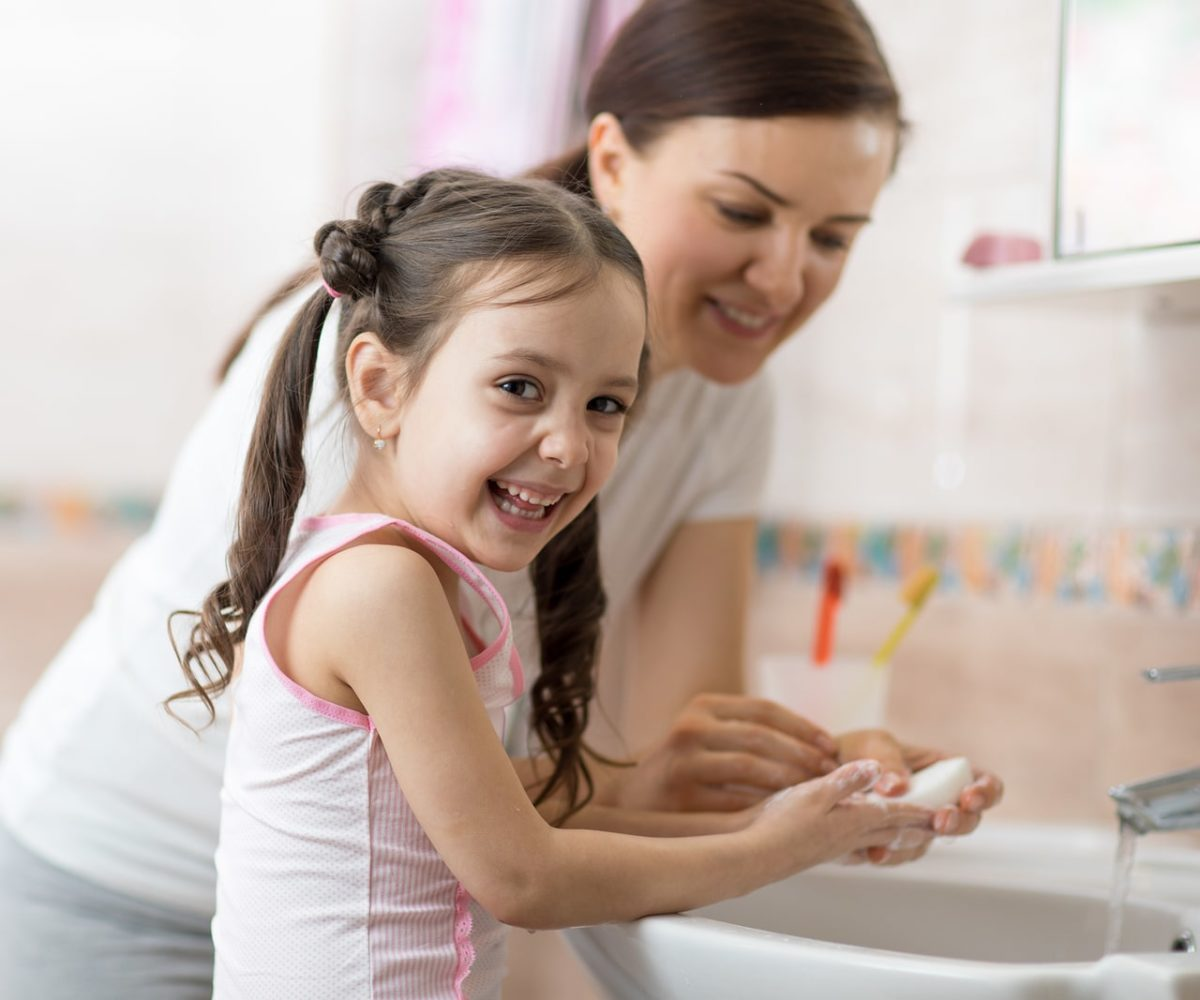 A young girl learning how to wash her hands with her mom