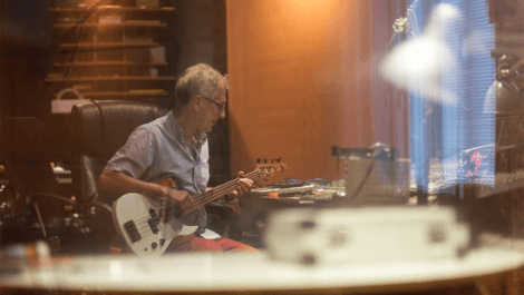 Man playing an electric guitar in a recording studio.