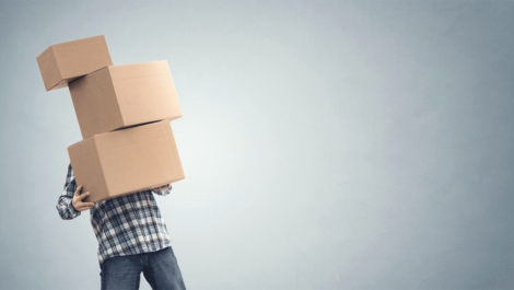 Man struggling to carry three stacked moving boxes.