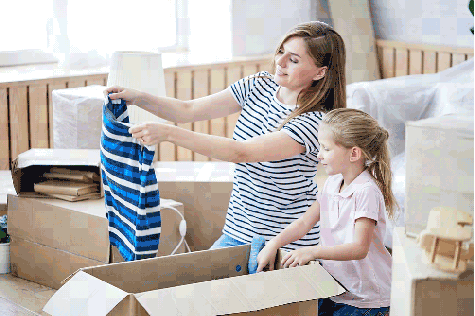 Mother and daughter filling moving boxes.